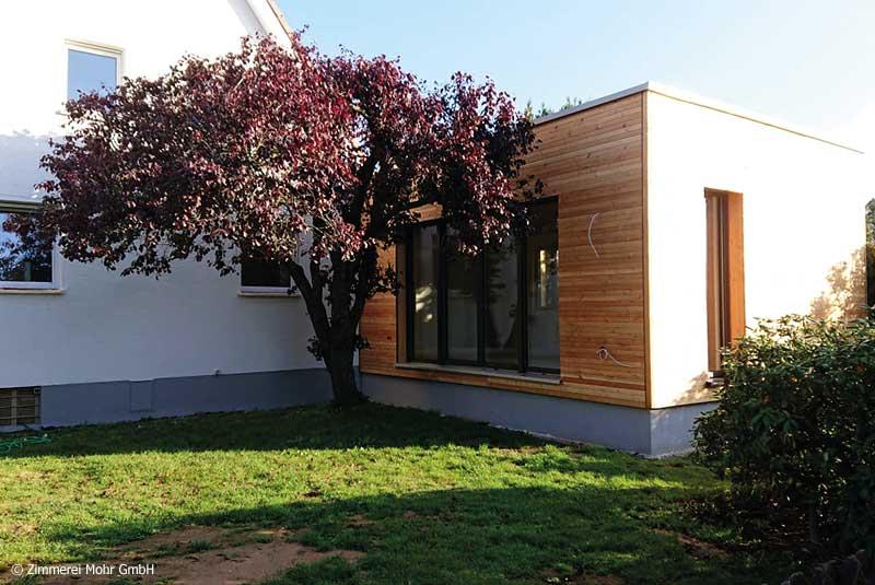 Flachdachanbau an Wohnhaus mit Holzfassade