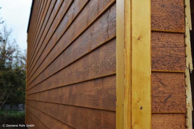 Holzfassade aus lasiertem Fichtenholz als Stülpschalung